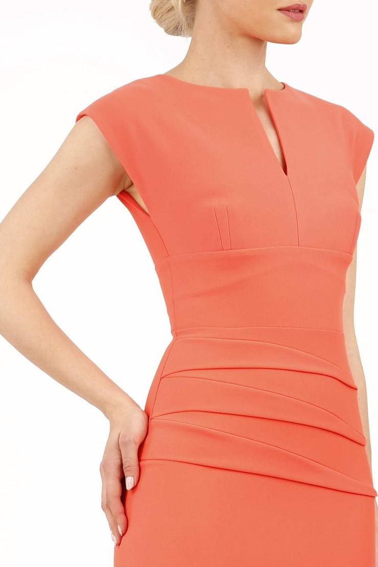 model wearing diva catwalk daphne sleeveless peach pencil dress with rounded neckline with split in the middle in front
