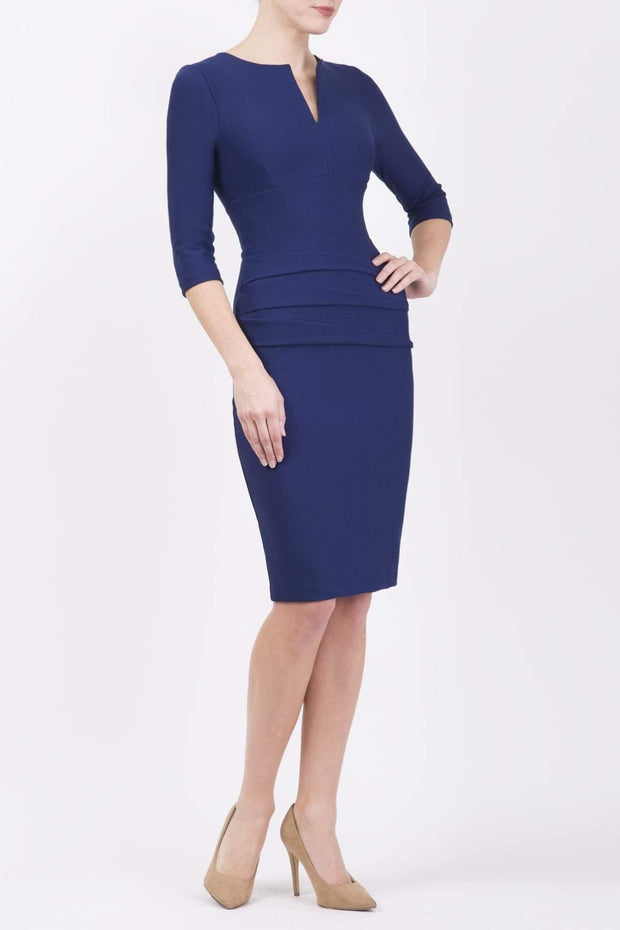 Model wearing the Diva Daphne ¾ Sleeved dress with pleat detail across the hips and ¾ sleeve length in navy front image