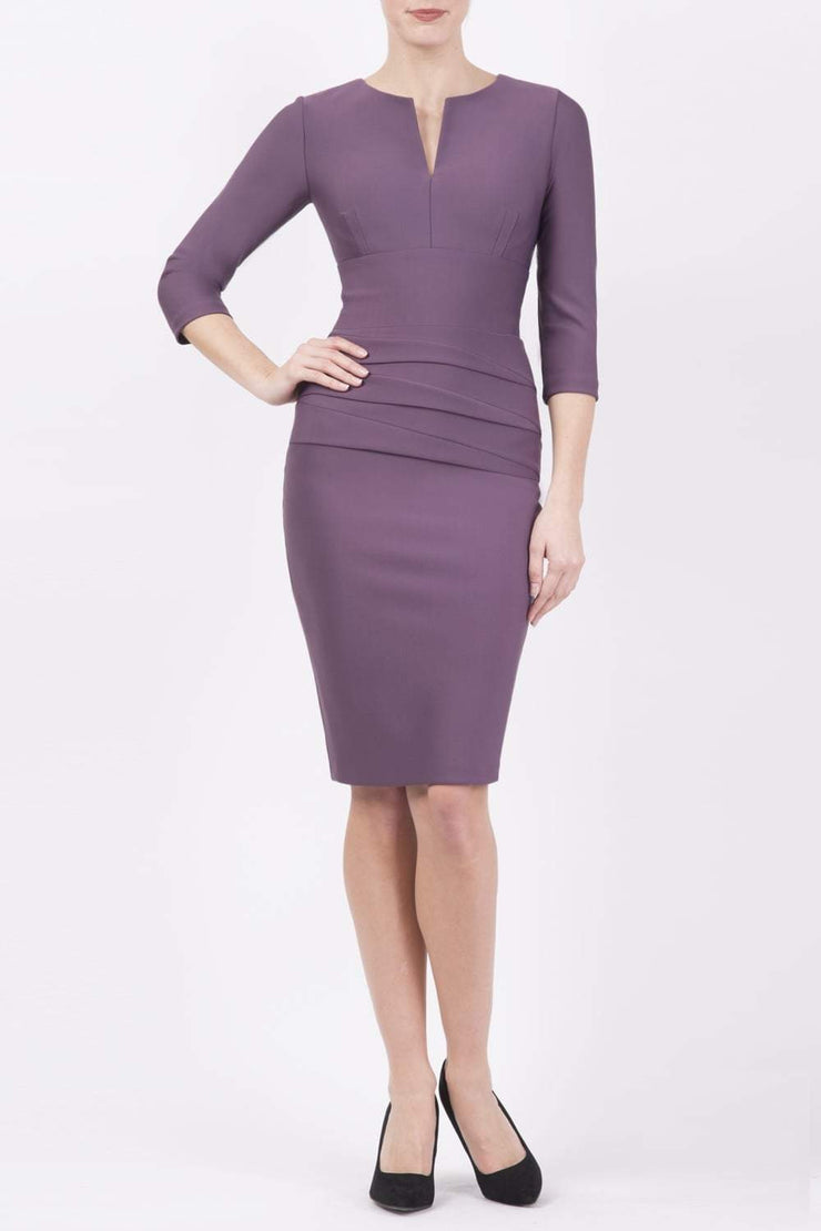 Model wearing the Diva Daphne ¾ Sleeved dress with pleat detail across the hips and ¾ sleeve length in mauve purple front