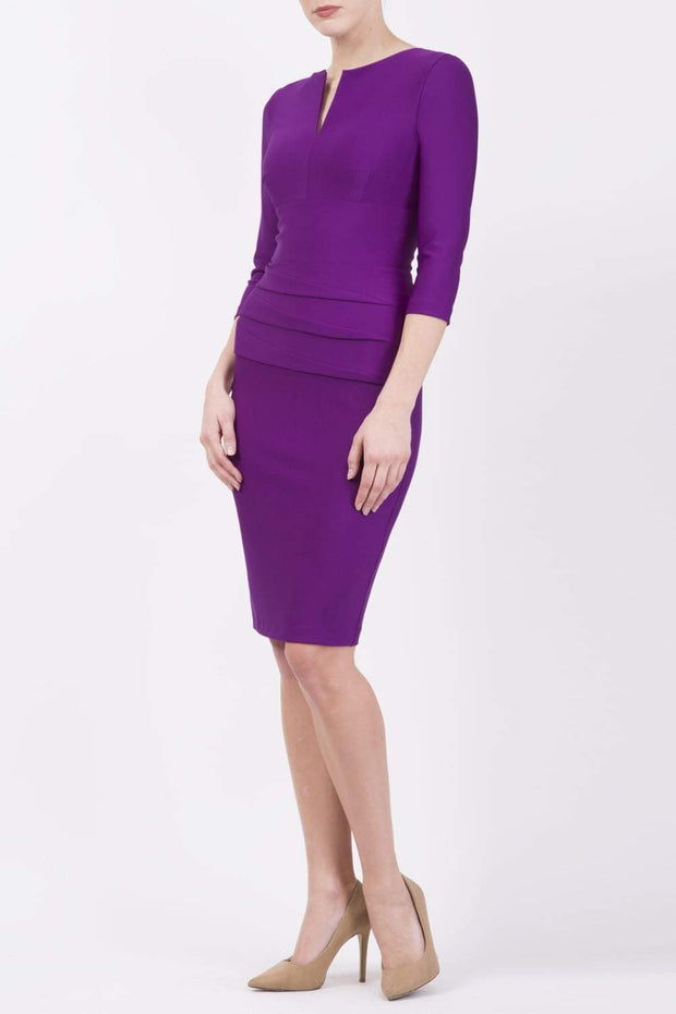 Model wearing the Diva Daphne ¾ Sleeved dress with pleat detail across the hips and ¾ sleeve length in purple magic front image