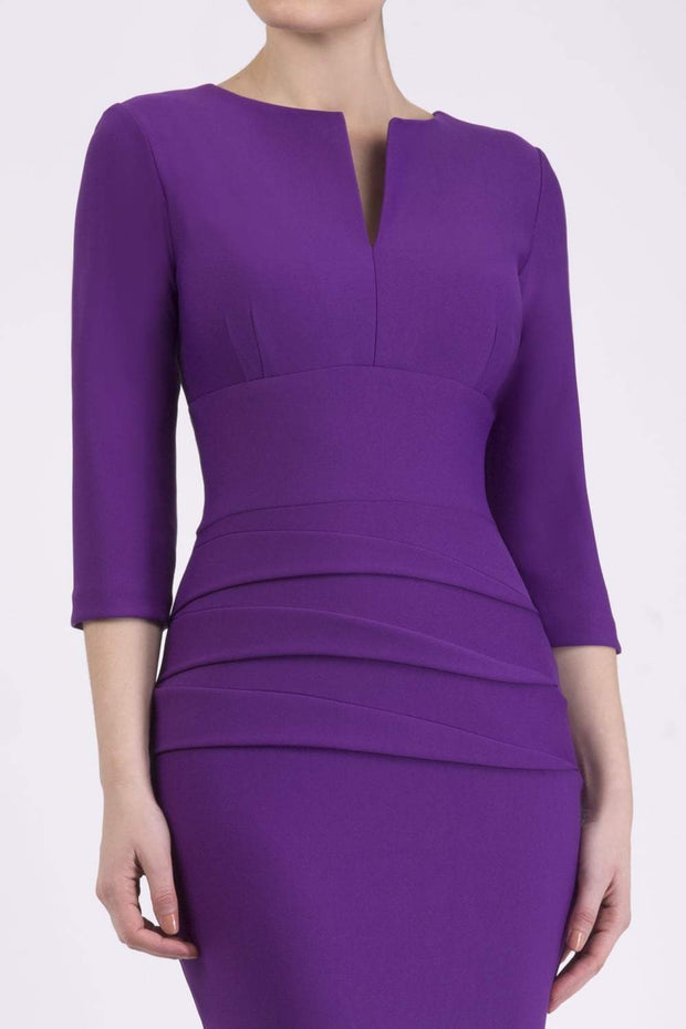 Model wearing the Diva Daphne ¾ Sleeved dress with pleat detail across the hips and ¾ sleeve length in royal purple front image