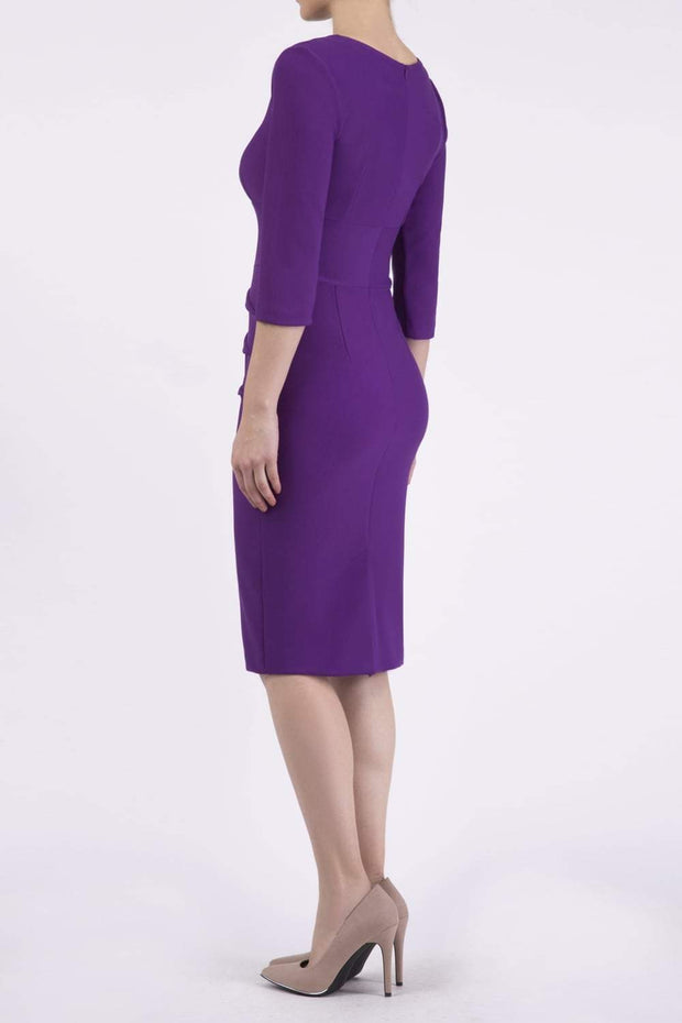 Model wearing the Diva Daphne ¾ Sleeved dress with pleat detail across the hips and ¾ sleeve length in royal purple back