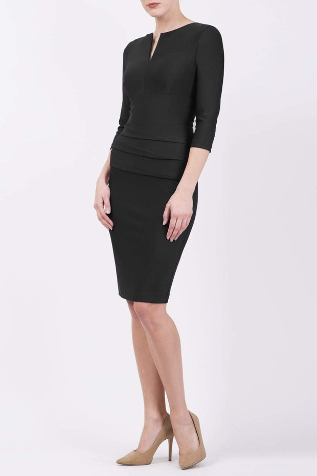 Model wearing the Diva Daphne ¾ Sleeved dress with pleat detail across the hips and ¾ sleeve length in black front