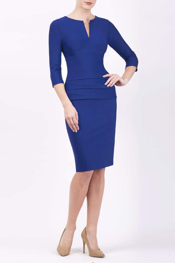 Model wearing the Diva Daphne ¾ Sleeved dress with pleat detail across the hips and ¾ sleeve length in cobalt blue front