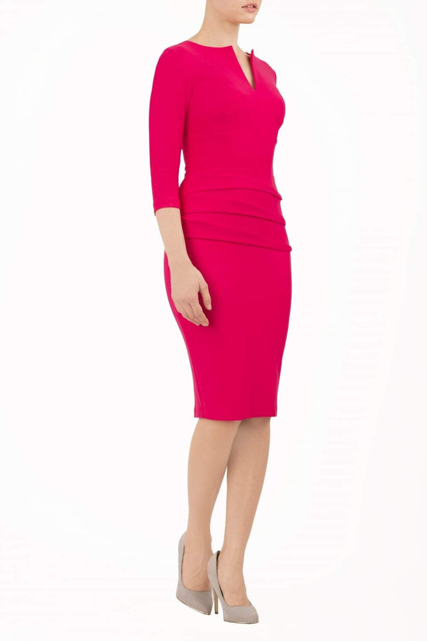 Model wearing the Diva Daphne ¾ Sleeved dress with pleat detail across the hips and ¾ sleeve length in yarrow pink front image