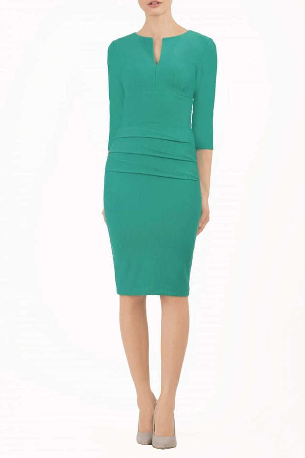 Model wearing the Diva Daphne ¾ Sleeved dress with pleat detail across the hips and ¾ sleeve length in emerald green front image