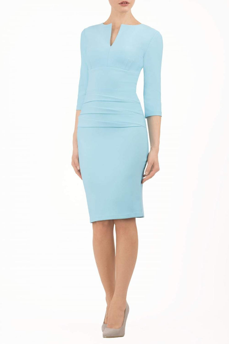 Model wearing the Diva Daphne ¾ Sleeved dress with pleat detail across the hips and ¾ sleeve length in sky blue front image
