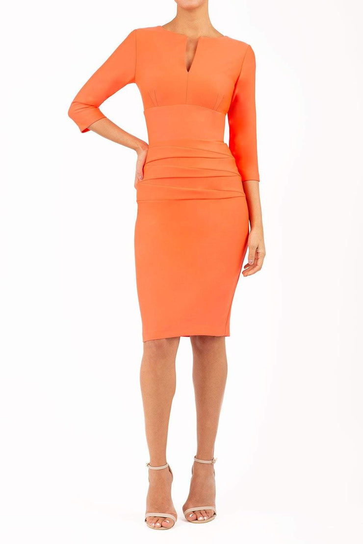 Model wearing Diva catwalk Daphne ¾ Sleeved pencil-skirt dress with pleat detail across the hips and ¾ sleeve length in hot coral front
