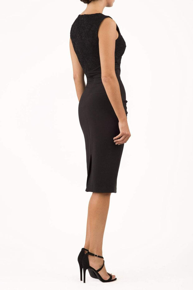 Model wearing the Diva Demelza Lace Pencil dress with lace stretch detailing and round neckline in black back image
