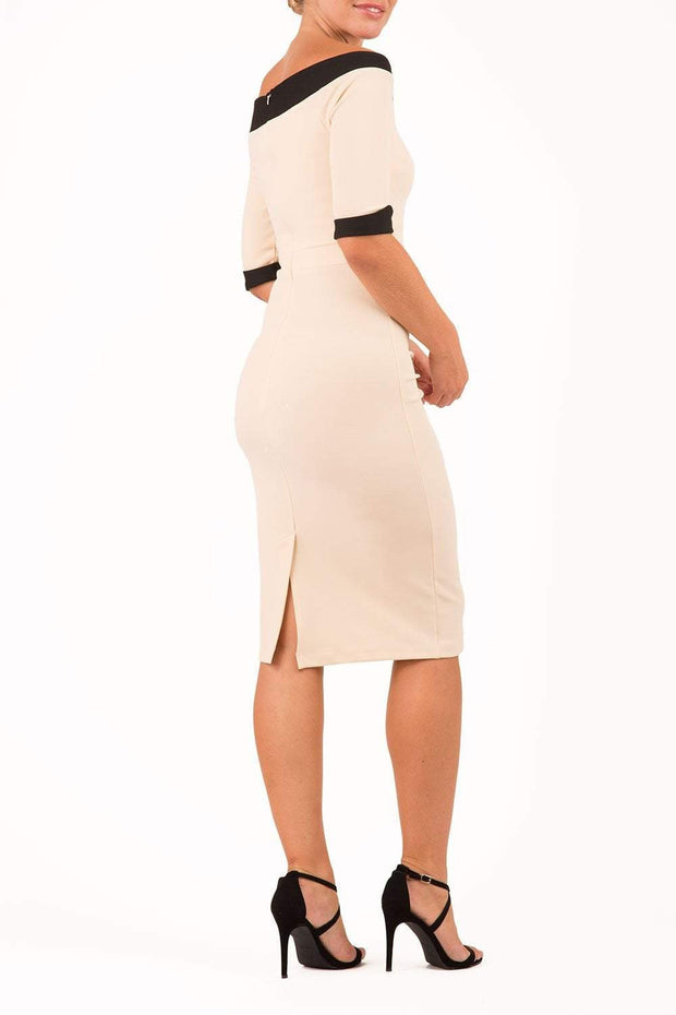 blonde model is wearing diva catwalk fellini sweetheart neckline fitted pencil dress with sleeves with cuff in colour beige with black contrasting detail back