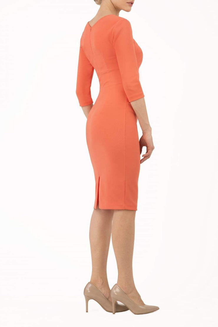 model wearing diva catwalk helston peach pencil dress with sleeves and cut out detail on the neckline back