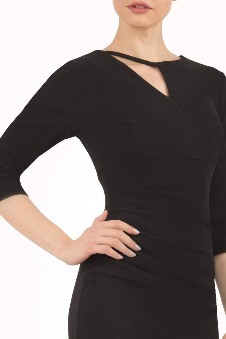 model wearing diva catwalk helston black pencil skirt  dress with sleeves and cut out detail on the neckline front