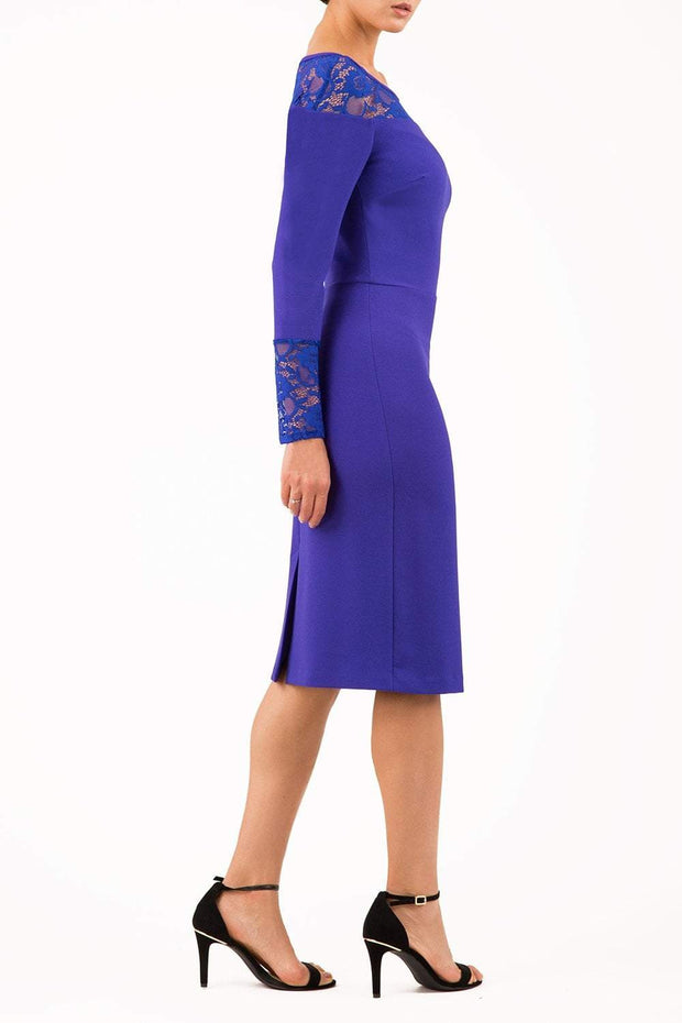 brunette model wearing diva catwalk blue lace pencil dress with long sleeves and rounded lace neckline with the lace covering shoulders side