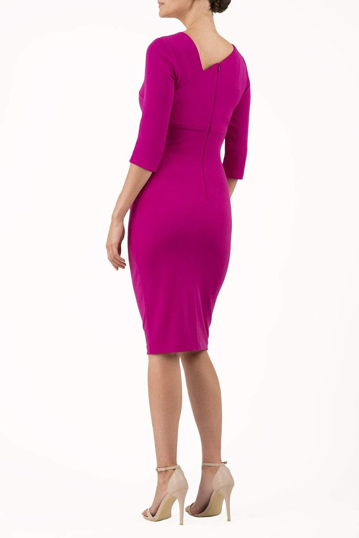 brinette model wearing diva catwalk kubrick pencil-skirt dress with sleeves and asymmetric neckline in magenta haze back