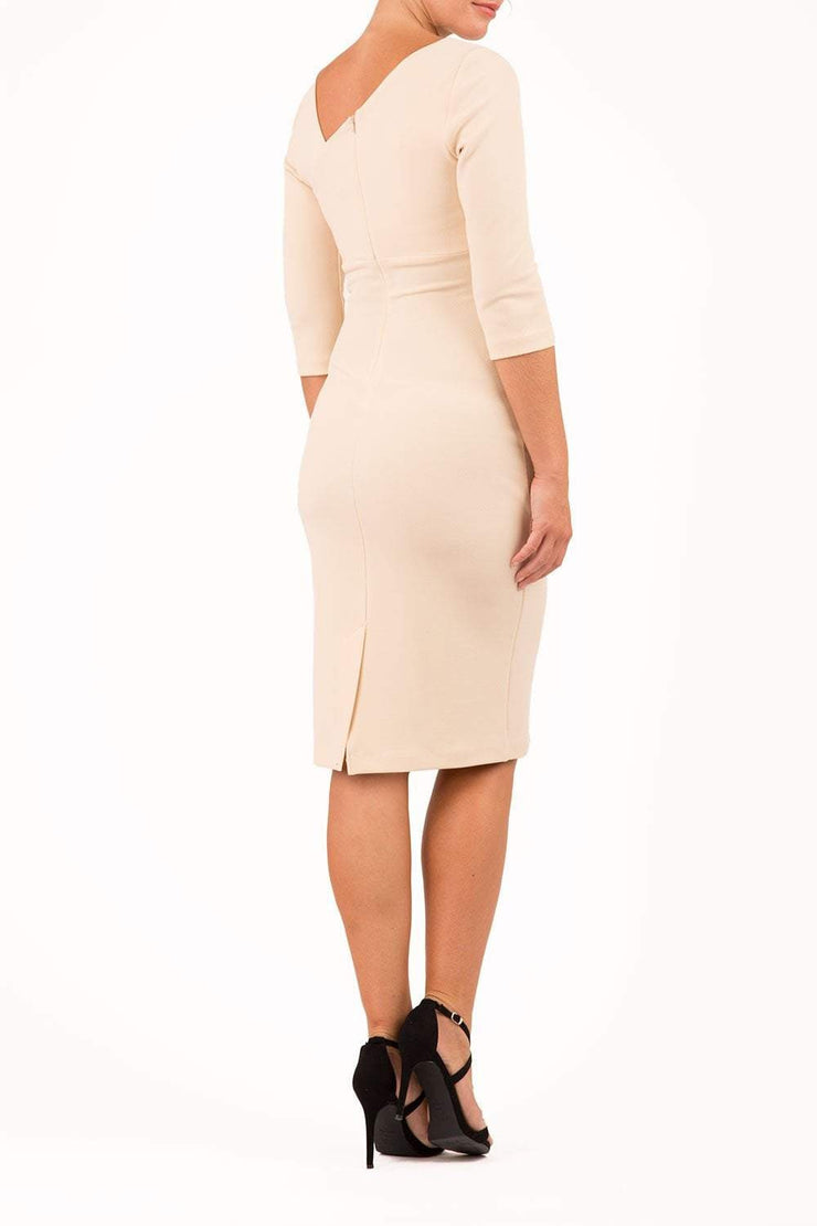 brinette model wearing diva catwalk kubrick pencil-skirt dress with sleeves and asymmetric neckline in beige back