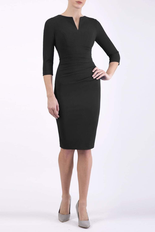brunette model wearing diva catwalk best selling lydia pencil sleeved dress with slit at the neckline and pleating across the tummy in colour black front
