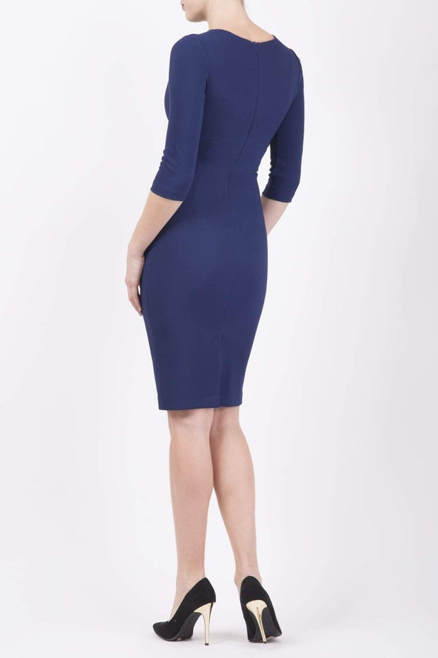 brunette model wearing diva catwalk best selling lydia pencil sleeved dress with slit at the neckline and pleating across the tummy in colour navy blue back
