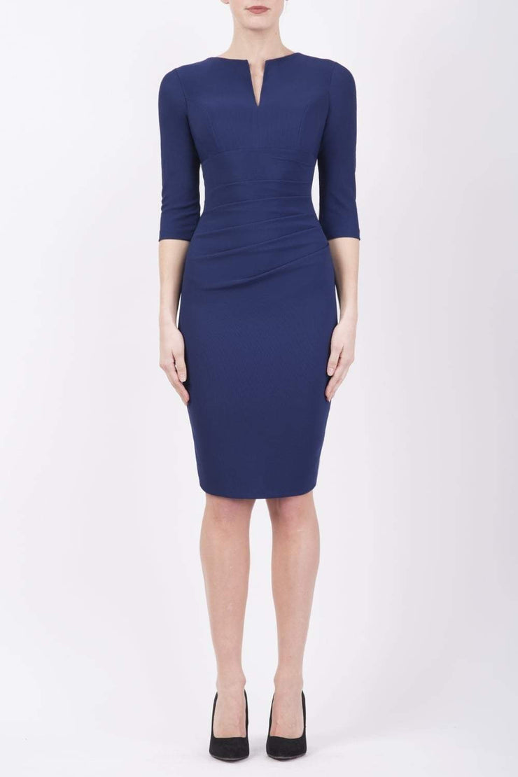 brunette model wearing diva catwalk best selling lydia pencil sleeved dress with slit at the neckline and pleating across the tummy in colour navy blue front