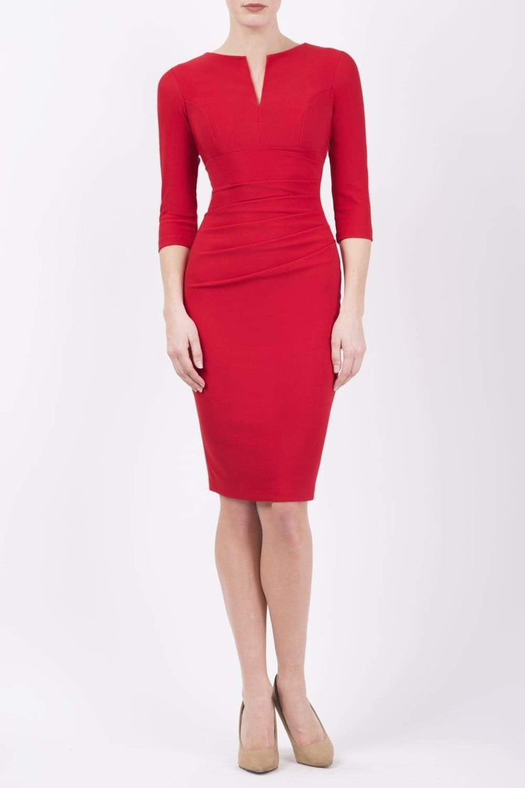 brunette model wearing diva catwalk best selling lydia pencil sleeved dress with slit at the neckline and pleating across the tummy in colour nrue red front