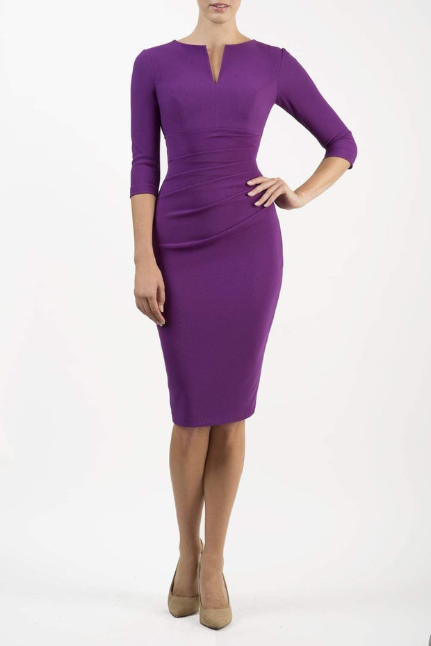 brunette model wearing diva catwalk best selling lydia pencil sleeved dress with slit at the neckline and pleating across the tummy in colour purple front