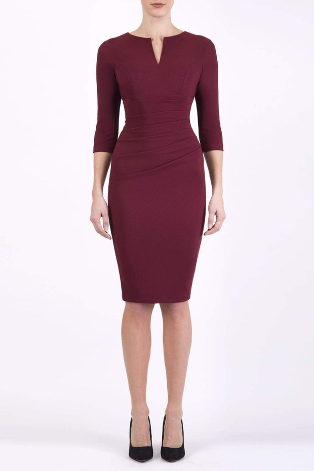 brunette model wearing diva catwalk best selling lydia pencil sleeved dress with slit at the neckline and pleating across the tummy in colour cabaret burgundy front