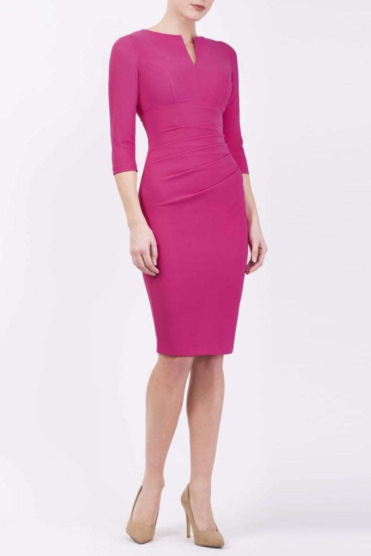 brunette model wearing diva catwalk best selling lydia pencil sleeved dress with slit at the neckline and pleating across the tummy in colour fuchsia pink front