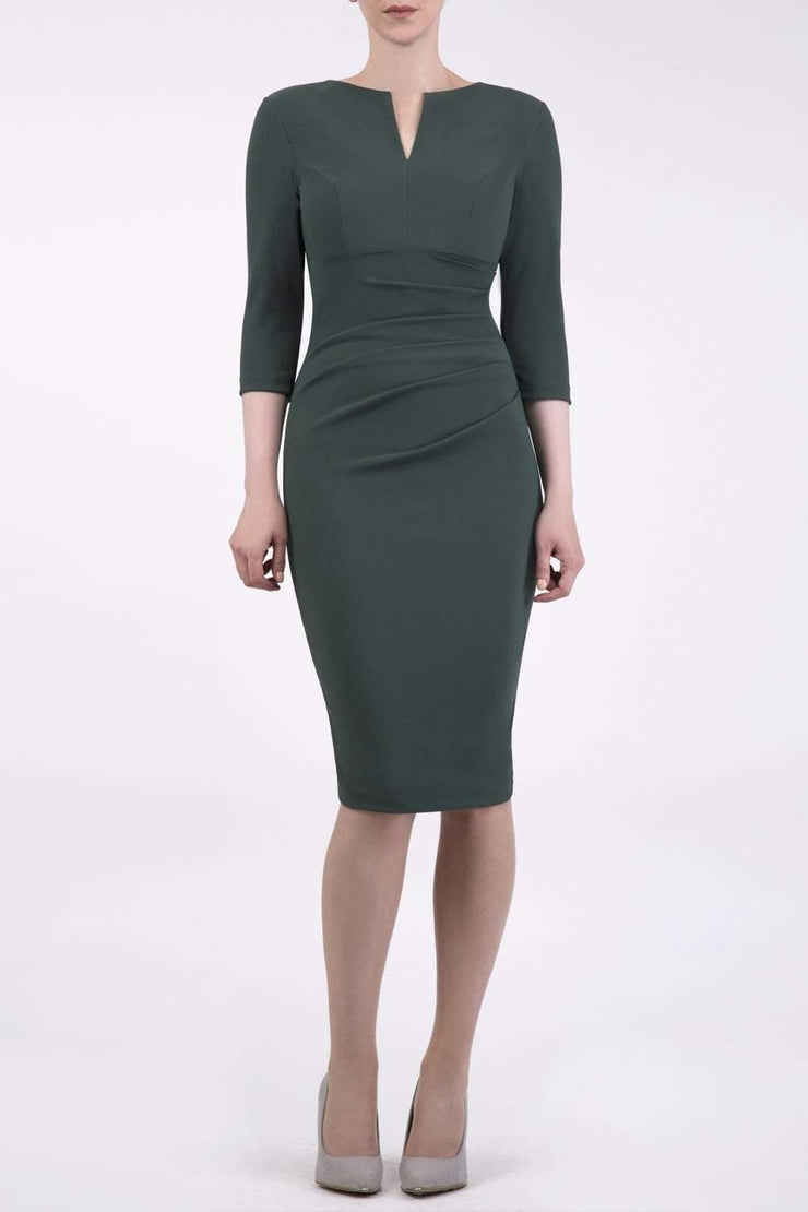 brunette model wearing diva catwalk best selling lydia pencil sleeved dress with slit at the neckline and pleating across the tummy in colour deep green  front