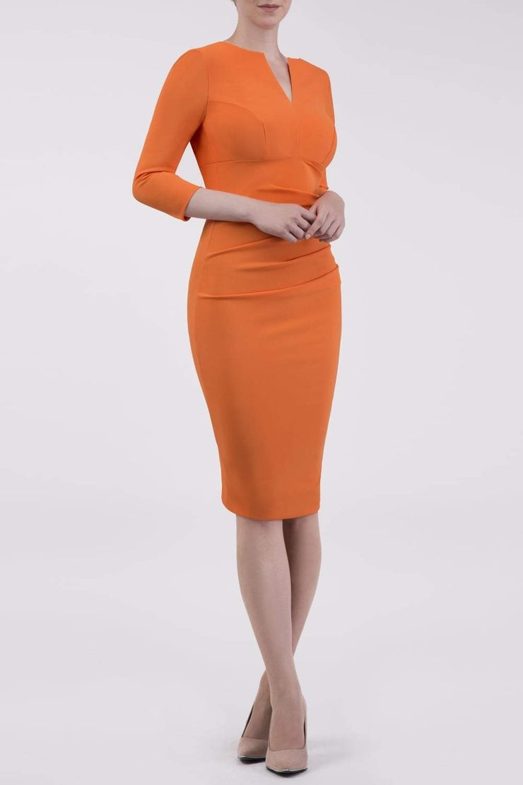 brunette model wearing diva catwalk best selling lydia pencil sleeved dress with slit at the neckline and pleating across the tummy in colour orange front