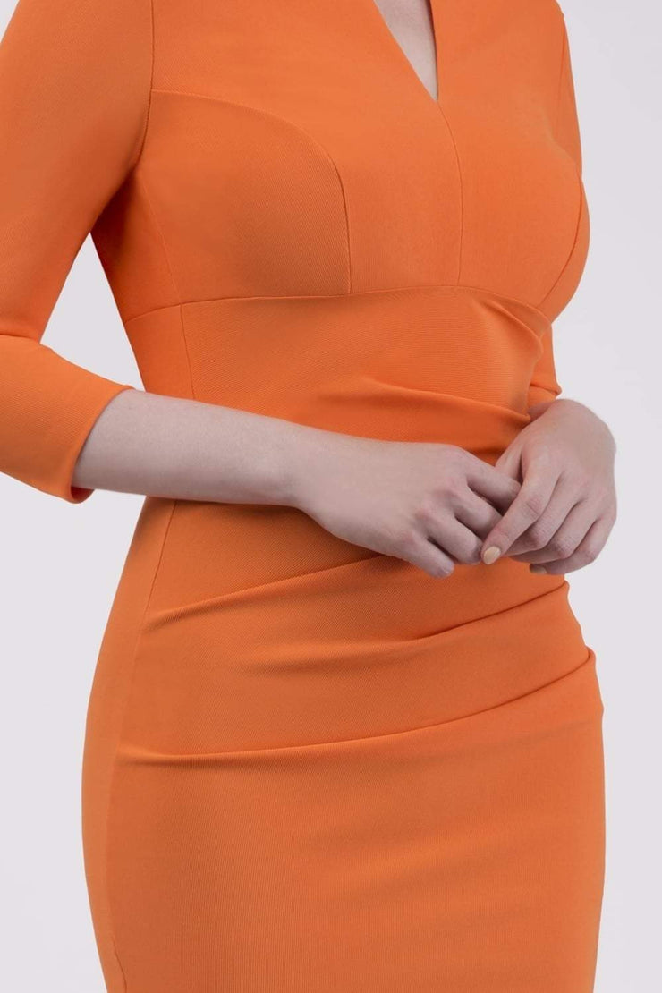 brunette model wearing diva catwalk best selling lydia pencil sleeved dress with slit at the neckline and pleating across the tummy in colour sun orange front