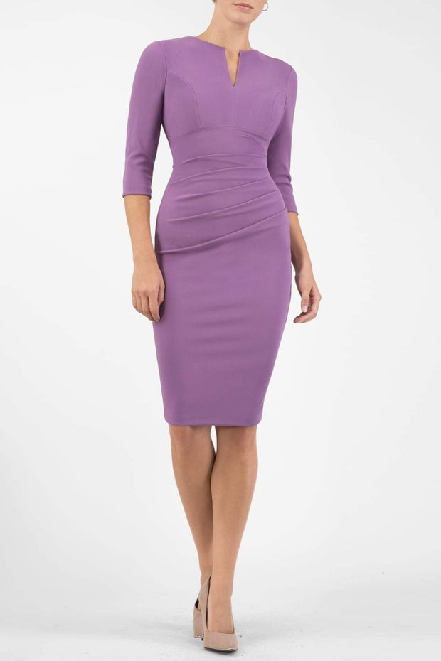 brunette model wearing diva catwalk best selling lydia pencil sleeved dress with slit at the neckline and pleating across the tummy in colour purple heart  front