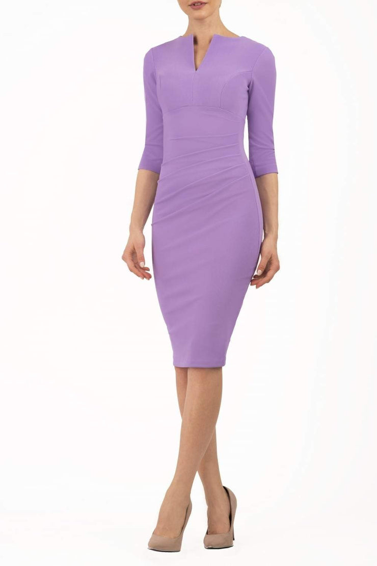 brunette model wearing diva catwalk best selling lydia pencil sleeved dress with slit at the neckline and pleating across the tummy in colour chalk purple front