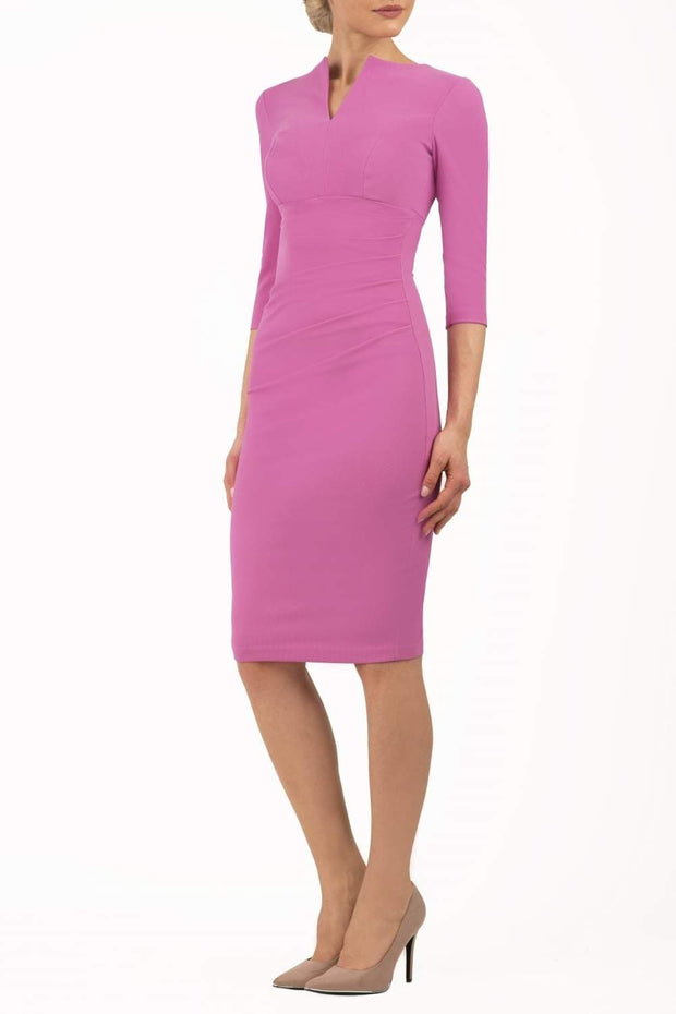 brunette model wearing diva catwalk best selling lydia pencil sleeved dress with slit at the neckline and pleating across the tummy in colour begonia pink front