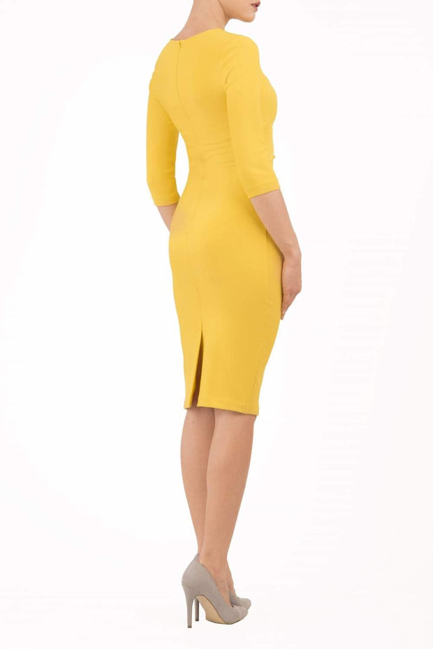 brunette model wearing diva catwalk best selling lydia pencil sleeved dress with slit at the neckline and pleating across the tummy in colour mustard yellow back