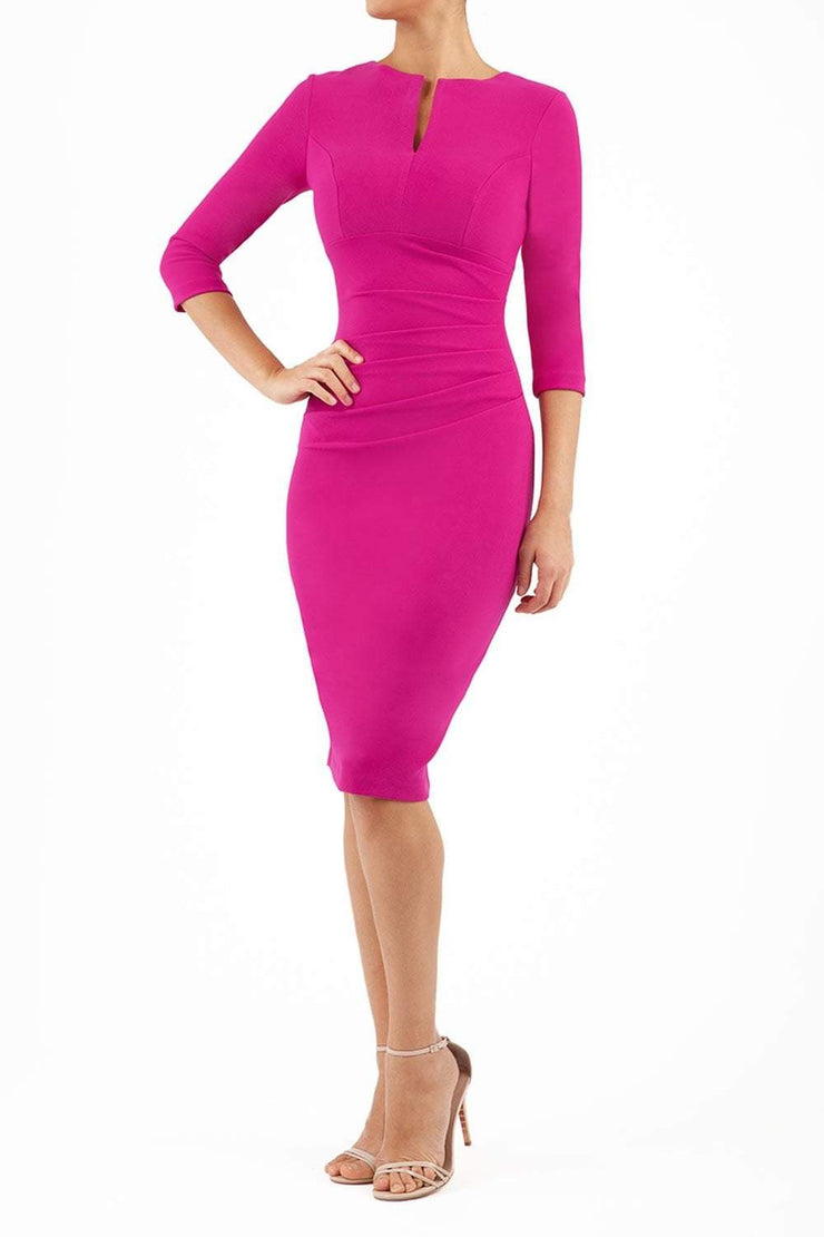 brunette model wearing diva catwalk best selling lydia pencil sleeved dress with slit at the neckline and pleating across the tummy in colour magenta pink front