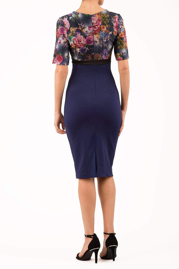 model wearing diva catwalk nadia fitted pencil dress made in the uk with short sleeves and pleated pencil skirt in navy and black back