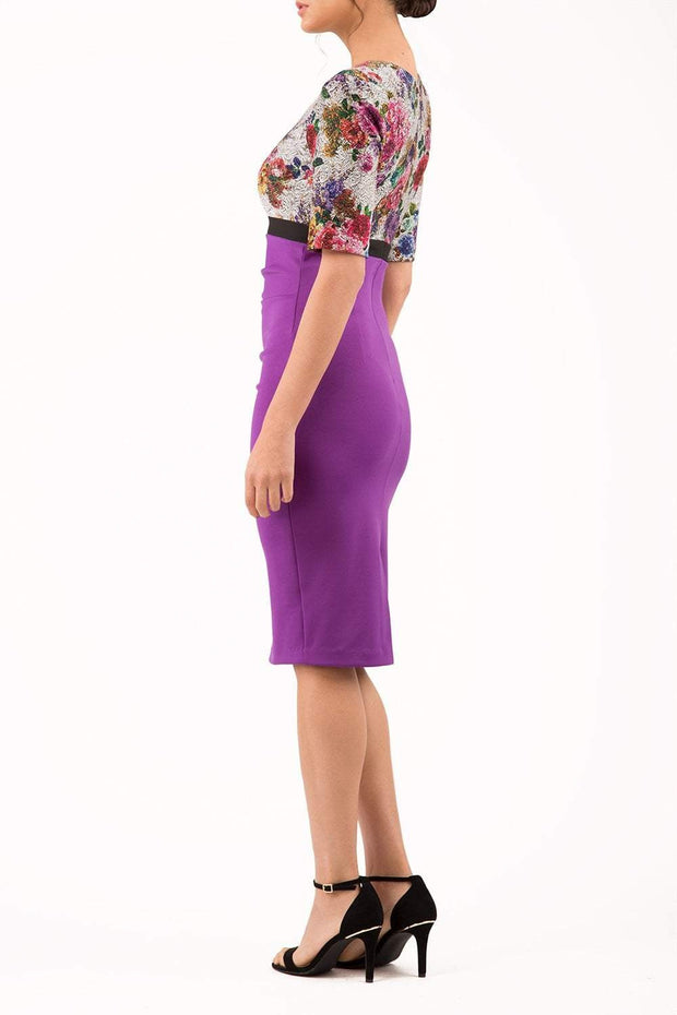 model wearing diva catwalk nadia fitted pencil dress made in the uk with short sleeves and pleated pencil skirt in purple and black front