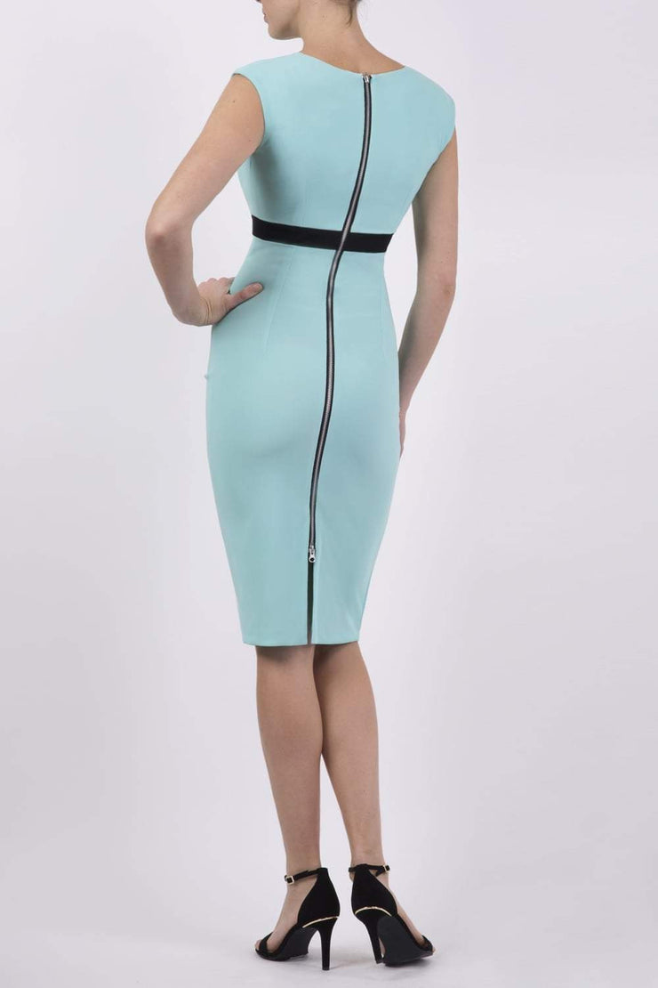 brunette model wearing diva catwalk nadia sleeveless pencil dress in mint green colour with a contrasting black band and exposed zip at the back with a rounded neckline with a slit  in the middle back