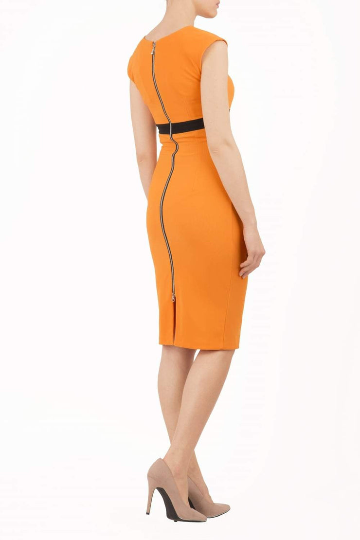 brunette model wearing diva catwalk nadia sleeveless pencil dress in sun orange colour with a contrasting black band and exposed zip at the back with a rounded neckline with a slit  in the middle back