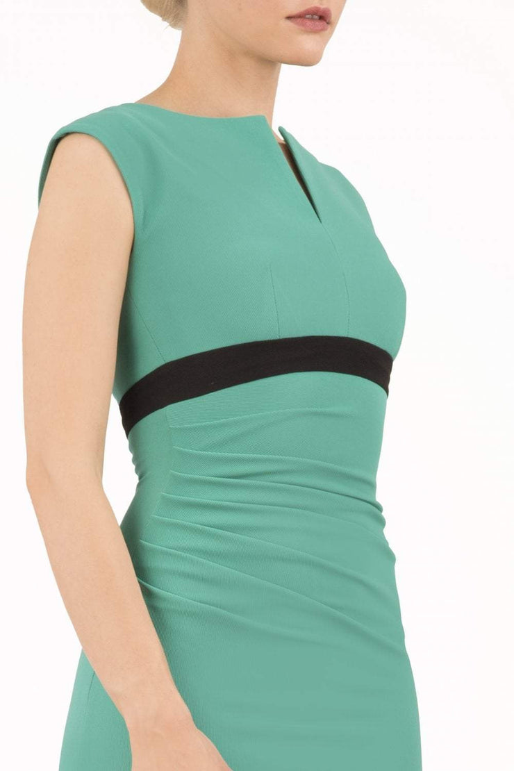 brunette model wearing diva catwalk nadia sleeveless pencil dress in emerald green colour with a contrasting black band and exposed zip at the back with a rounded neckline with a slit  in the middle front