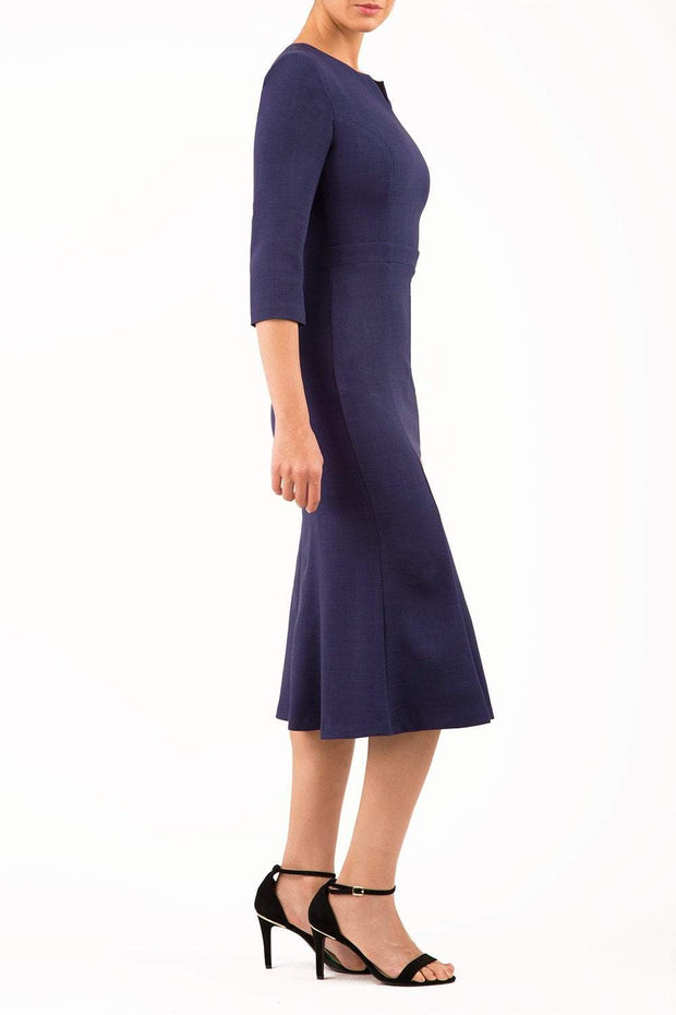 blonde model is wearing diva catwalk senne midaxi sleeved dress with fishtail and rounded neckline with a slit in the middle in navy blue side