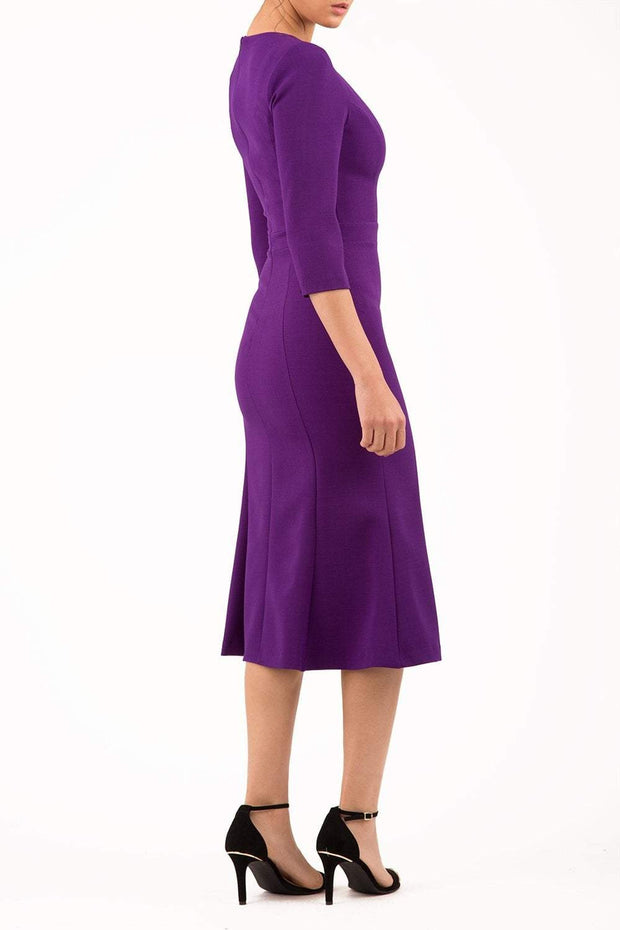 blonde model is wearing diva catwalk senne midaxi sleeved dress with fishtail and rounded neckline with a slit in the middle in royal purple side