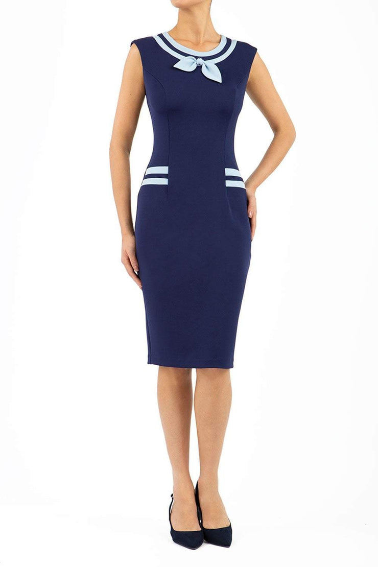 model wearing diva catwalk navy blue tempo pencil dress with pocket detail and rounded neckline with bow detail front