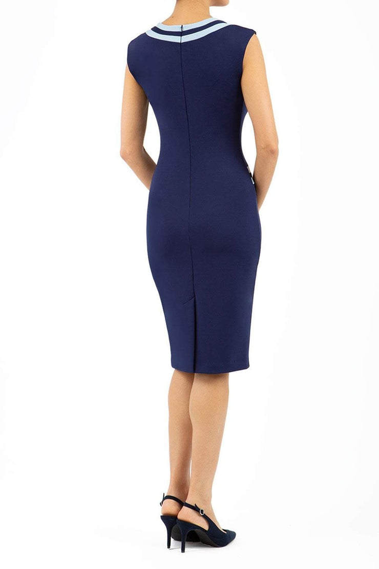 model wearing diva catwalk navy blue tempo pencil dress with pocket detail and rounded neckline with bow detail back