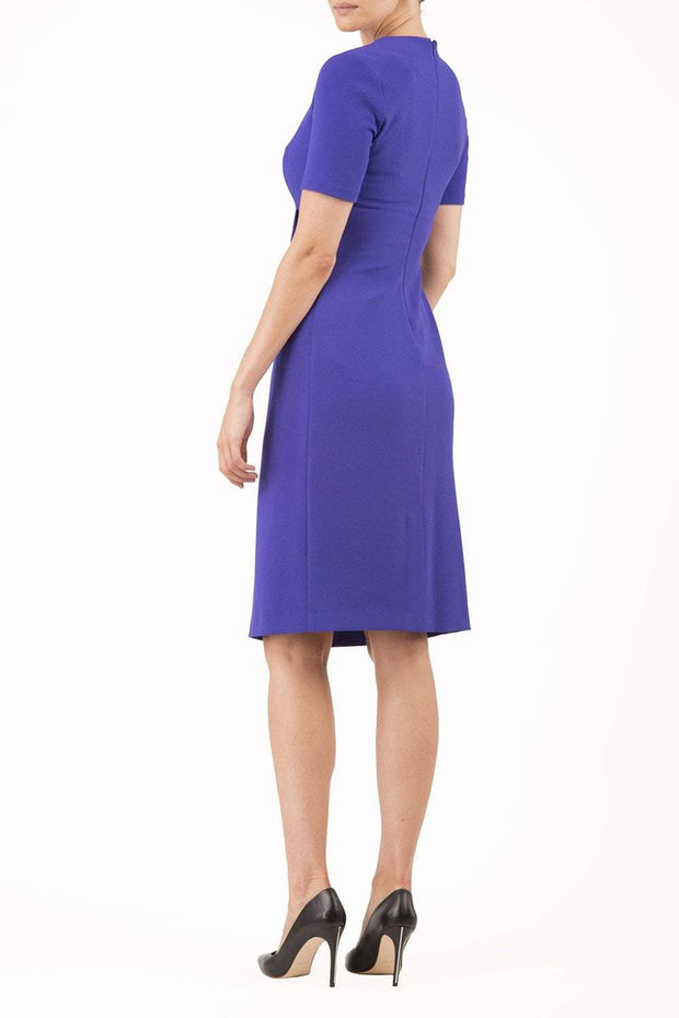 brunette model wearing diva catwalk tregony a-line dress with lowered v-neckline in spectrum indigo and short sleeves back