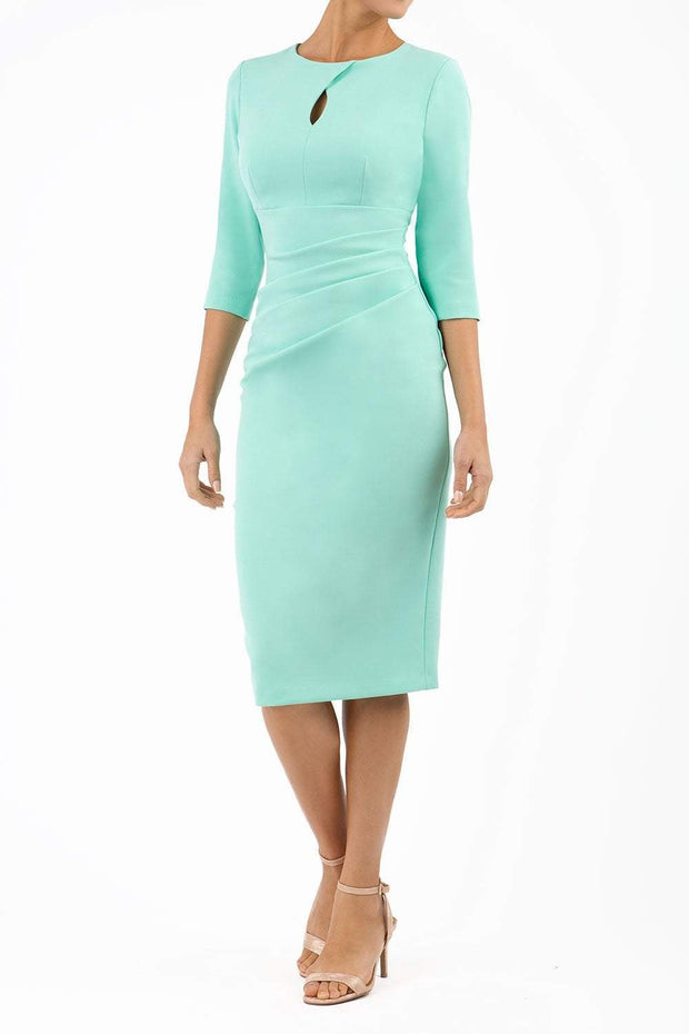 brunette model wearing diva catwalk ubrique pencil dress with a keyhole detail and sleeves in mint green front