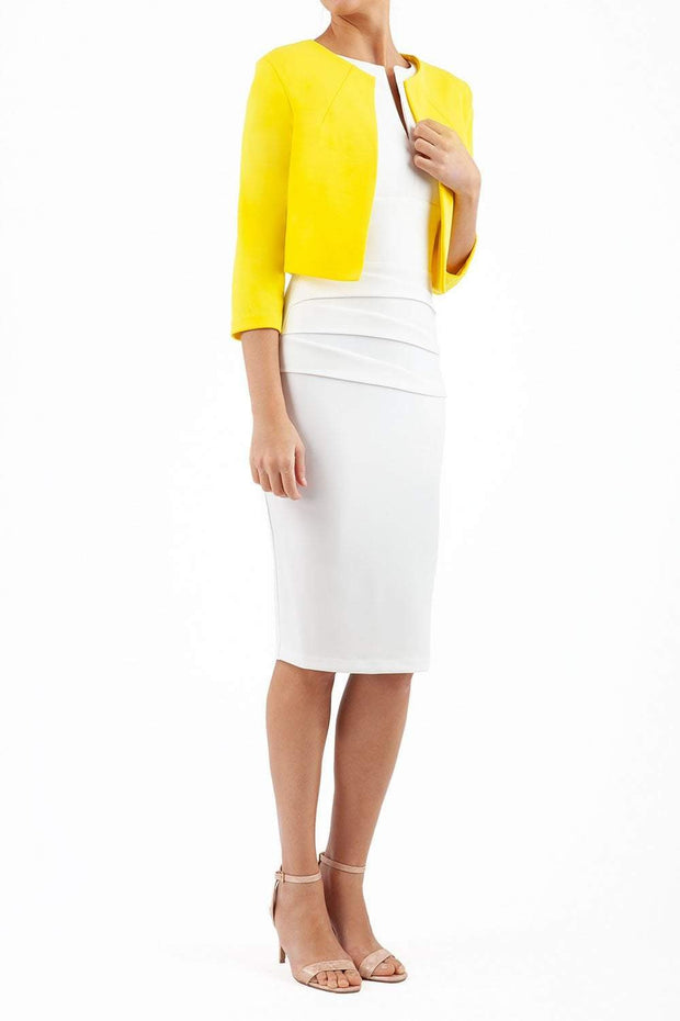 brunette model wearing diva catwalk yellow sleeved bolero over a white pencil dress front
