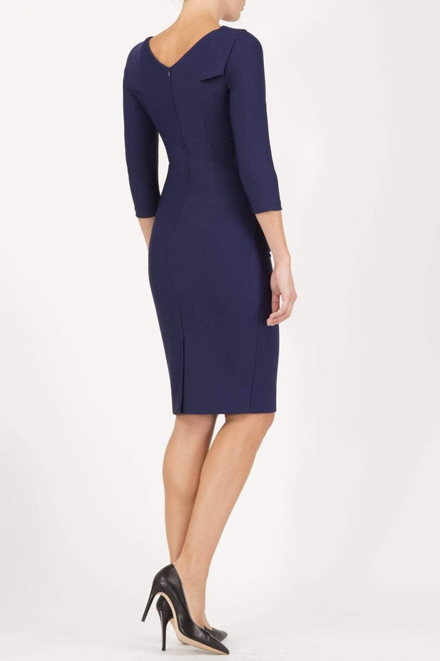 model wearing diva catwalk york pencil-skirt dress with sleeves and rounded folded collar and plearing across the tummy area in navy blue colour back