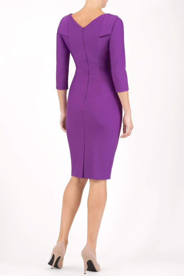 model wearing diva catwalk york pencil-skirt dress with sleeves and rounded folded collar and plearing across the tummy area in royal purple colour back