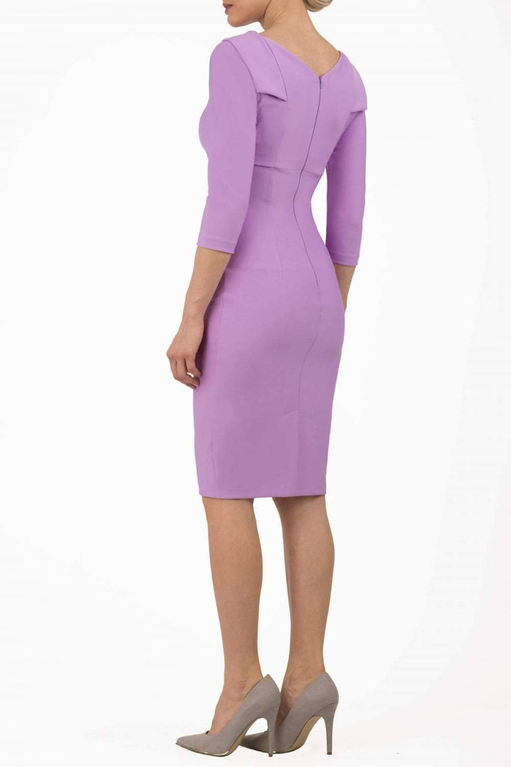 model wearing diva catwalk york pencil-skirt dress with sleeves and rounded folded collar and plearing across the tummy area in violet bloom colour back