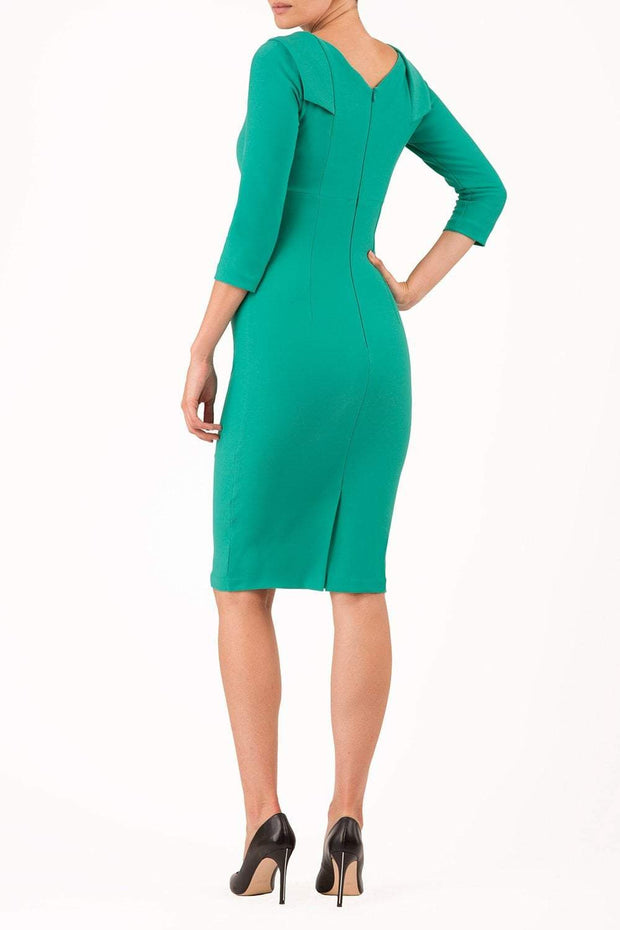 model wearing diva catwalk york pencil-skirt dress with sleeves and rounded folded collar and plearing across the tummy area in emerald green colour back